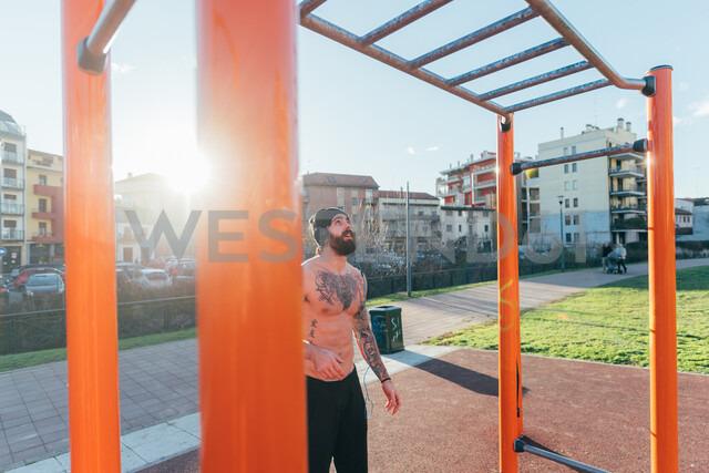 Man contemplating horizontal ladder in outdoor gym - CUF47405