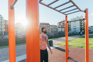 Man contemplating horizontal ladder in outdoor gym - CUF47405