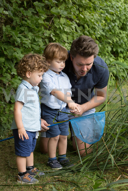 Father and children looking in fishing net - CUF47420