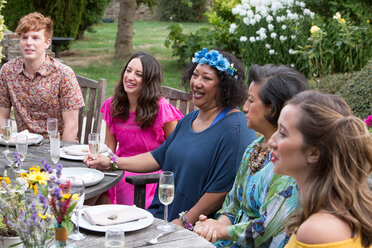 Guests enjoying and celebrating at garden party - CUF47441