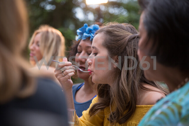 Guests enjoying and celebrating at garden party - CUF47447