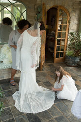 Bride's wedding dress being arranged - CUF47459