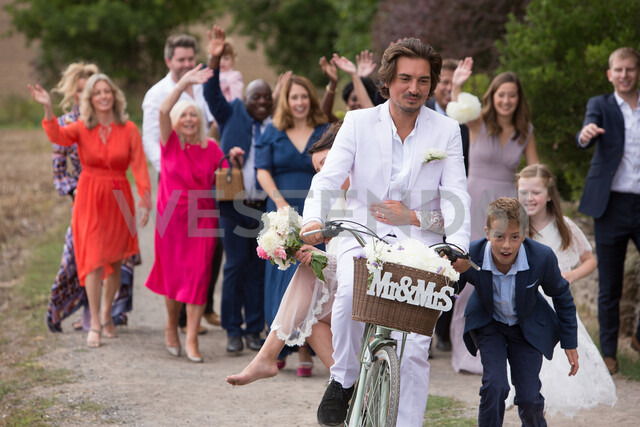 Wedding guests waving off newlyweds on bicycles - CUF47462 - Jim Forrest/Westend61