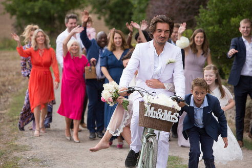 Wedding guests waving off newlyweds on bicycles - CUF47462