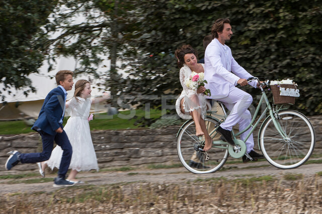 Young wedding guests running after newlyweds on bicycles - CUF47465