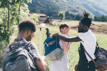 Three young adult hiking friends preparing rucksacks in field - CUF47495