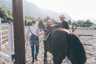 Young woman leading horse in rural equestrian arena - CUF47498