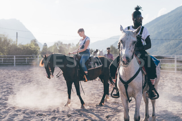 Young hipster man and woman riding horses in rural equestrian arena, Primaluna, Trentino-Alto Adige, Italy - CUF47504