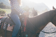 Young woman riding horse in sunlit equestrian arena, cropped, Primaluna, Trentino-Alto Adige, Italy - CUF47507