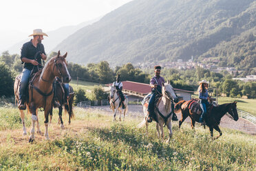 Young adults riding horses in rural landscape, Primaluna, Trentino-Alto Adige, Italy - CUF47516