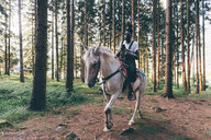 Cool young man horse riding in forest,  Primaluna, Trentino-Alto Adige, Italy - CUF47519