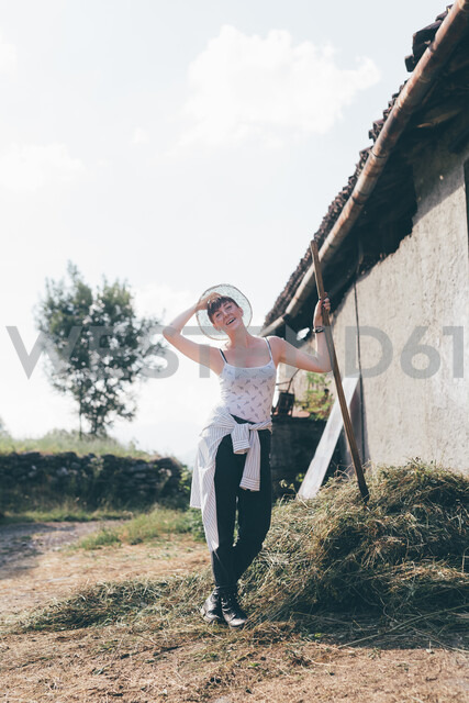 Young female agricultural worker with pitchfork, full length portrait - CUF47528