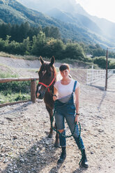 Young woman leading horse in rural equestrian arena, full length portrait - CUF47531