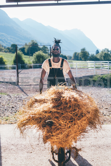Cool young man with wheelbarrow hay in rural equestrian arena, portrait - CUF47534