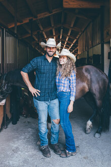 Young cowgirl and boyfriend at stable entrance, portrait - CUF47537
