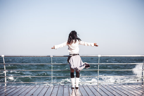 Mid adult woman looking out from pier with arms open, rear view, Odessa, Odeska Oblast, Ukraine - CUF47540