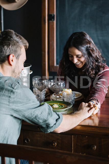 Romantic young couple having a meal, holding hands across table - CUF47552