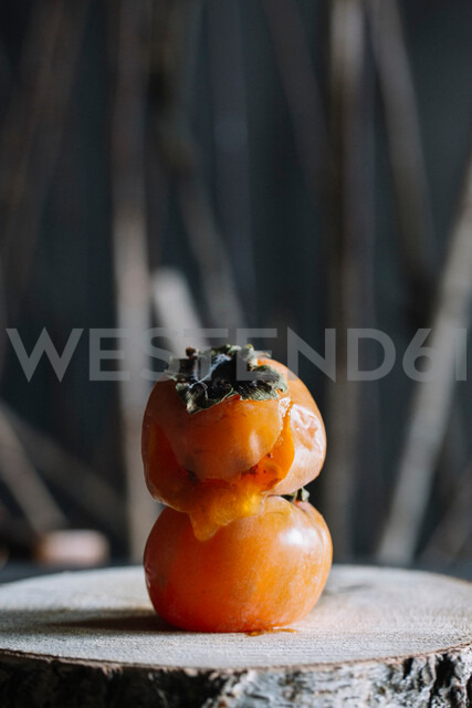 Persimmon fruit on top of another on rustic cutting board - CUF47555