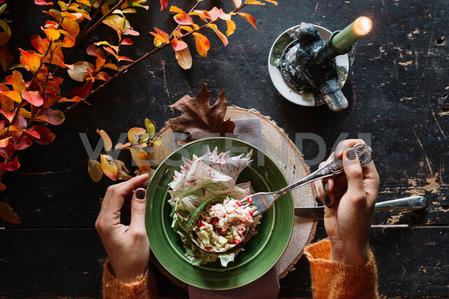 Woman eating fresh salad at vintage table, overhead view of hands - CUF47567