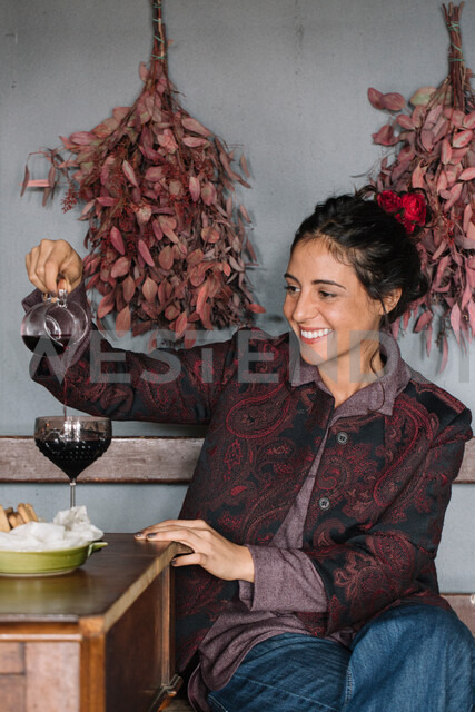 Young woman at rustic table pouring red wine - CUF47573 - Alberto Bogo/Westend61