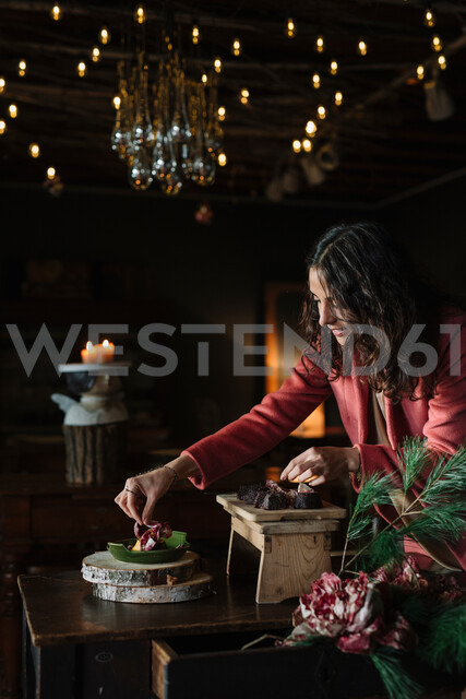 Young woman at rustic table garnishing food - CUF47576