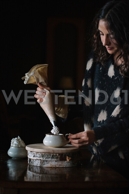 Young woman piping cream into bowl using piping bag - CUF47582