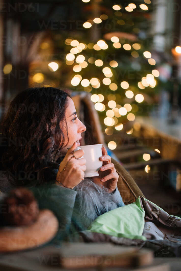 Young woman drinking coffee in cafe with decorative lights - CUF47585 - Alberto Bogo/Westend61