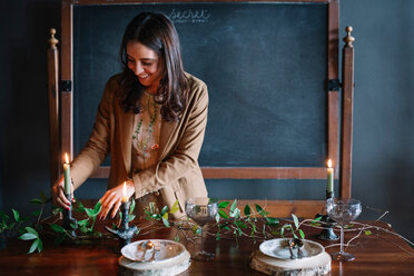 Young woman decorating vintage dinner table with candle and foliage - CUF47588