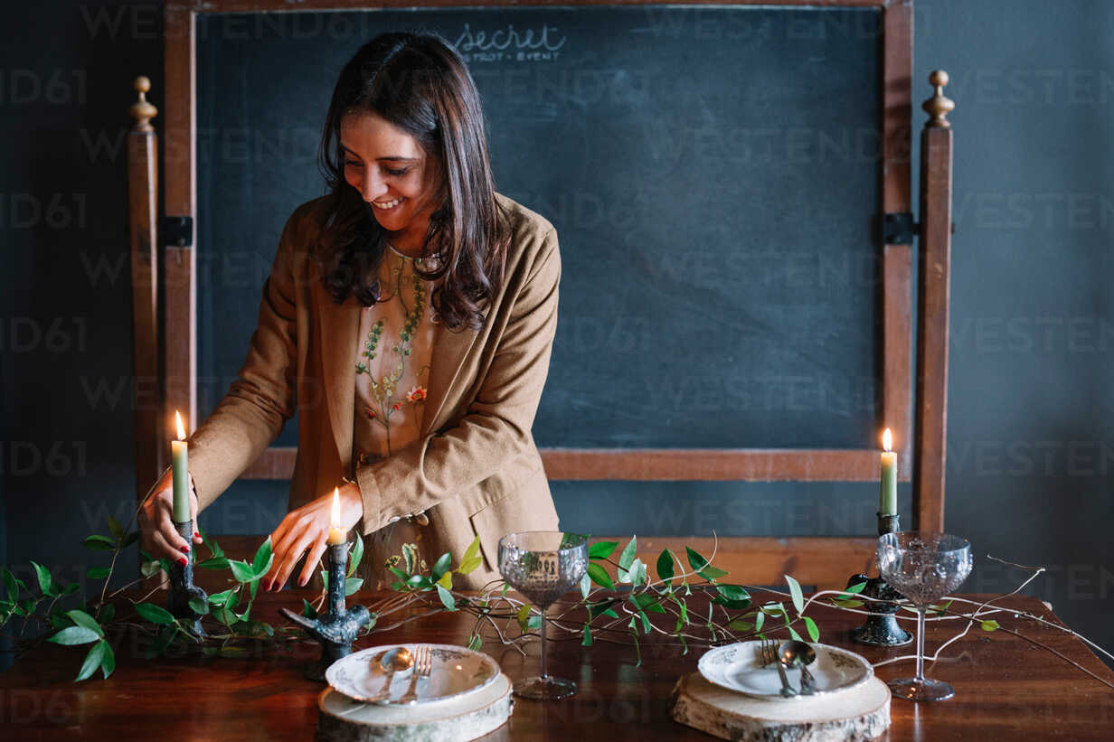 Young woman decorating vintage dinner table with candle and foliage - CUF47588 - Alberto Bogo/Westend61