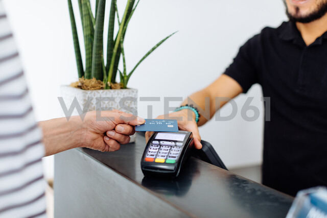 Male hairstylist taking male customer's credit card payment at hair salon, cropped - CUF47591