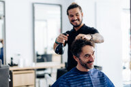 Male hairstylist spraying male customer's hair in hair salon - CUF47597