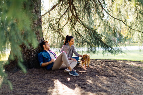 Couple with pet dog sitting by large tree - CUF47612