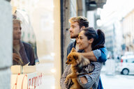 Couple with pet dog window-shopping, Milan, Italy - CUF47615