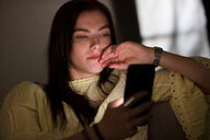 Teenage girl sitting on sofa in dark reading text message - CUF47669