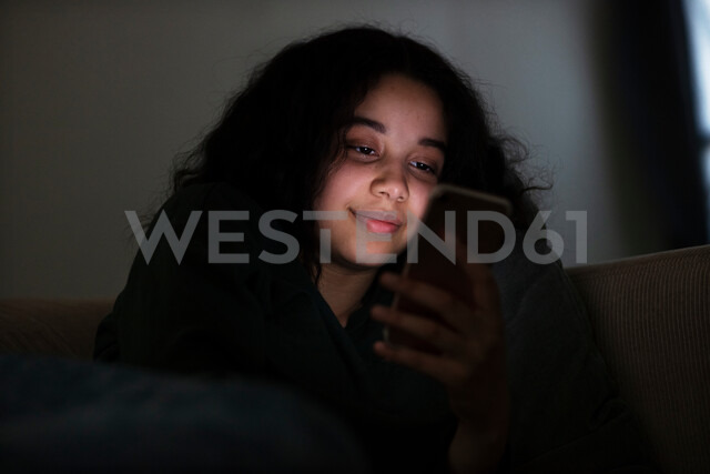 Teenage girl sitting on sofa in dark reading text message - CUF47672 - T2 Images/Westend61