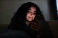 Teenage girl sitting on sofa in dark reading text message - CUF47672