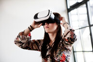 Teenage girl looking through virtual reality handset - CUF47678