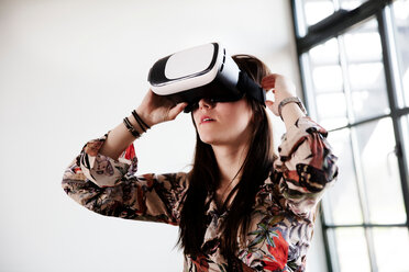 Teenage girl looking through virtual reality handset - CUF47678