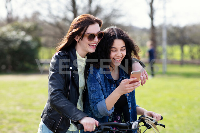 Teenage girls reading text together on push bike - CUF47681 - T2 Images/Westend61