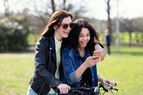 Teenage girls reading text together on push bike - CUF47681