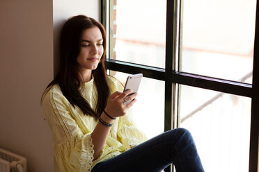 Teenage girl reading text message on cellphone by glass window - CUF47687