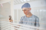 Teenage boy reading text message on cellphone by glass wall - CUF47696