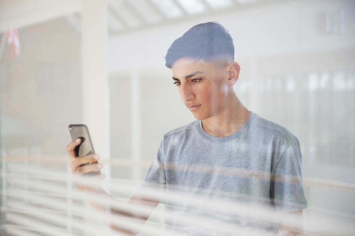 Teenage boy reading text message on cellphone by glass wall - CUF47696 - T2 Images/Westend61