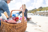 Sisters enjoying picnic on beach - CUF47714