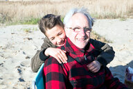 Senior adult man with grandson enjoying beach - CUF47735