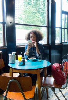 Woman using cellphone by cafe window, London, UK - CUF47750