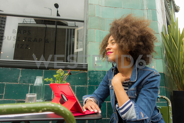 Woman looking up from digital tablet at pavement cafe, London, UK - CUF47759