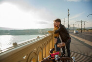 Couple on bridge with bicycles, Budapest, Hungary - CUF47777