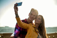 Couple taking selfie on bridge, Budapest, Hungary - CUF47780