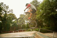 BMX cyclist doing stunt on ramp - CUF47798